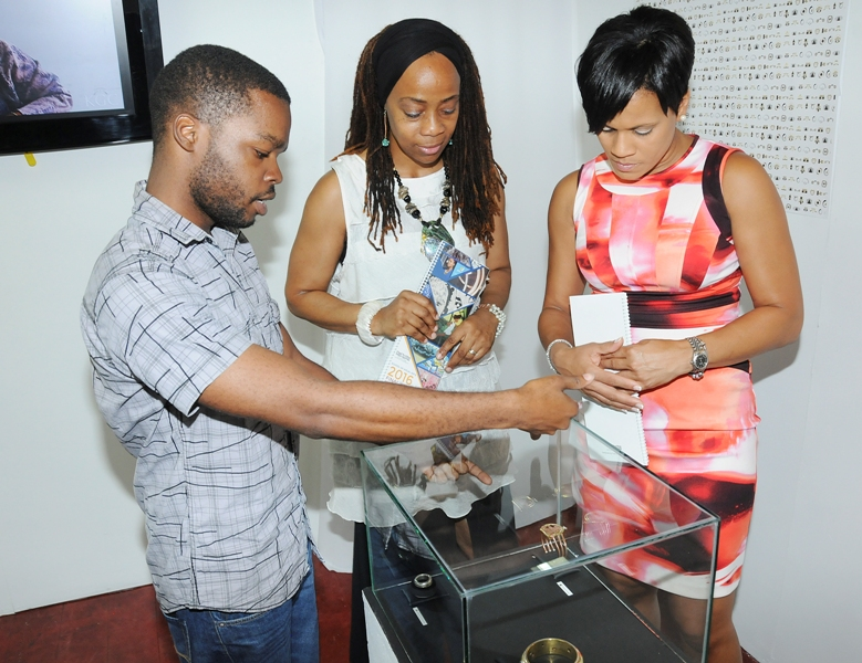 Keenan Clarke, (left) final year student at the Edna Manley College of the Visual and Performing Arts explains how he incorporated Jamaica proverbs into his jewellery to Gillian Hyde (right) General Manager, JN Small Business Loans and Miriam Smith, Director, School of the Visual Arts. The occasion was the launch of the School of the Visual Arts Final Year Exhibition held at Edna Manley College in 2016. Clarke was the only jewellery student in his class.