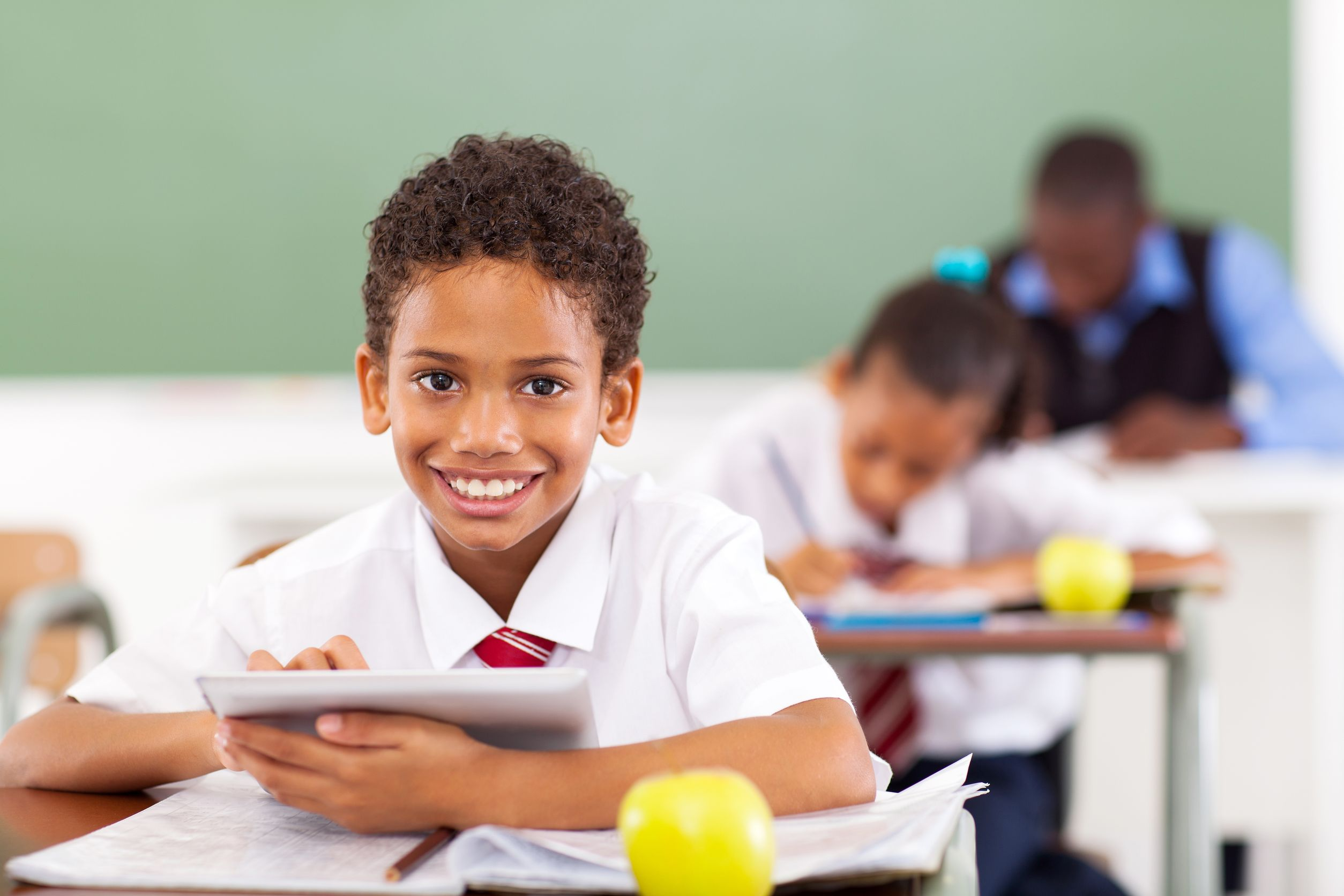 primary school boy using tablet in classroom