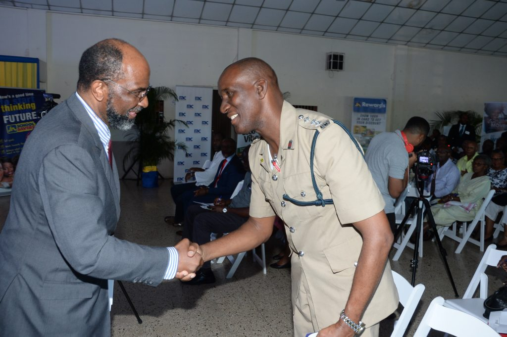 """Earl Jarrett (left), Chief Executive Officer, The Jamaica National Group, greets Deputy Superintendent Owen Brown of the May Pen Police Station at The JN Group Community Security Forum, """"Creating Safer Spaces for your Family"""", held at the St. Gabriel's Anglican Church Hall, on January 29, 2019. The outreach initiative supports the police in their crime-fighting efforts."""
